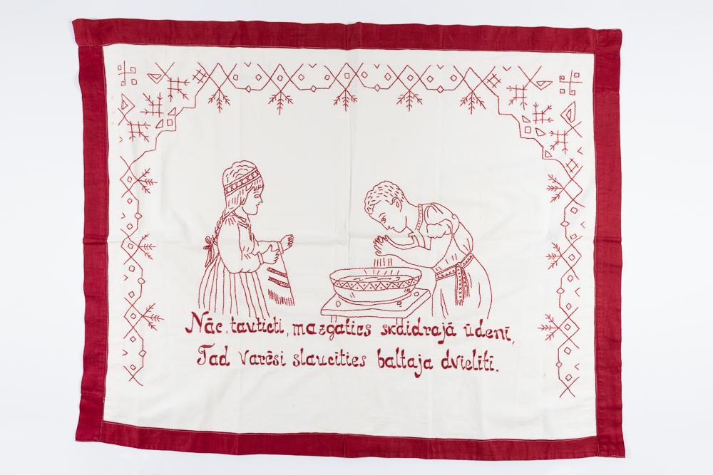 """Virtuves sienas dekors ar sižetisku zīmējumu - puisis mazgājas, meita tur dvieli, apakšā uzraksts: """"Nāc, tautieti, mazgāties skaidrajā ūdenī, Tad varēsi slaucīties baltajā dvielītī"""". Izšuvusi Lilija Mona (Šmēdiņa) (1931-2002) Vandzenes pag., 1950. gadi"""