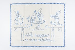 """Sienas dekors ar izšūtu zīmējumu – trīs rūķi darbībā un uzrakstu ziliem diegiem """"Nāc mazgājies no ūdens nebaidies"""", 1930. gadi"""