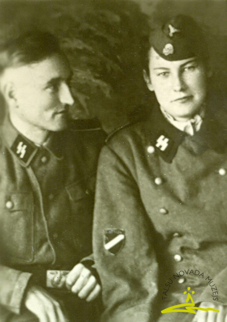 """6413 Leģionārs Arvīds Praznicāns Ādama d. (1912–1944) ar māsīcu Lidiju Irbi (Arvīda apģērbā) savā pēdējā atvaļinājumā Alūksnes rajona Liepnas pagasta """"Purnavās"""" leģionāra formas tērpā. Kritis 1944. gada 31. decembrī, apglabāts Talsos Jaunajos kapos"""