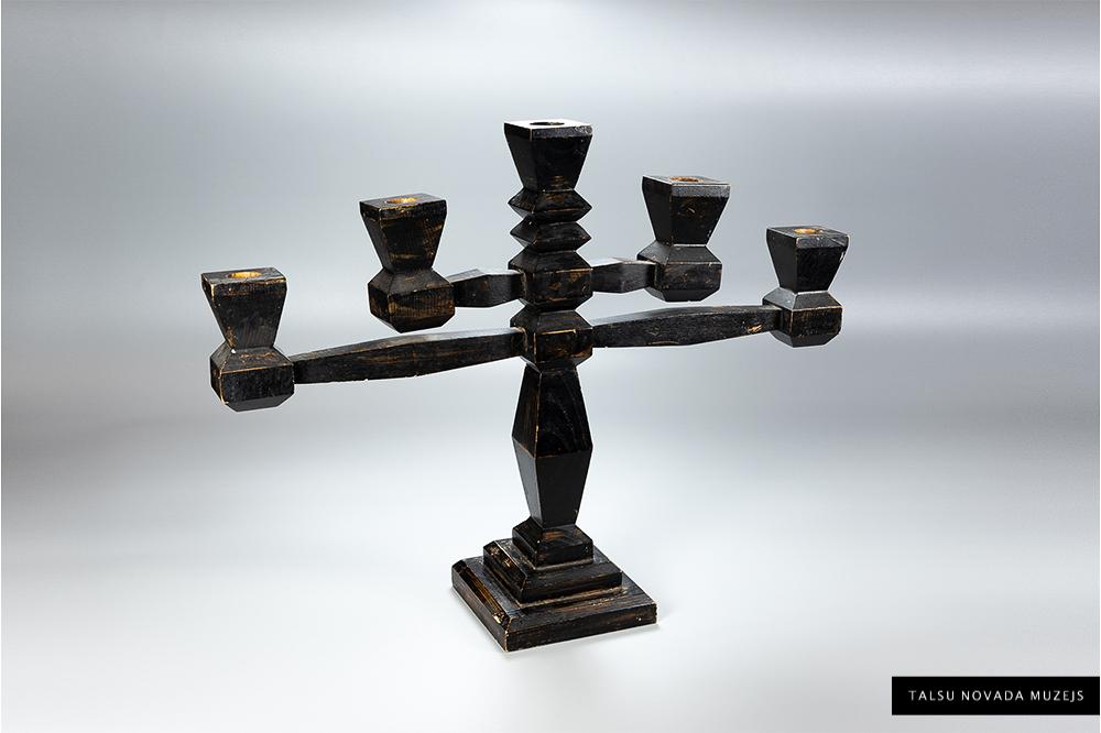 """Koka svečturis 5 svecēm, melni krāsots, apakšā spiedogs – """"Kultūra Talsos"""", 20. gs. 20. – 30.gadi. Piederējis skolotāja Grikmaņa ģimenei. TNMM 26150"""
