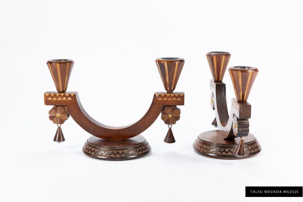 """Skaistie divžuburu svečturi, zem kuru ietvariem stilizētas saulītes figūras ar dzintaru centrā, piederējuši Talsu 2. astoņgadīgās skolas skolotājai Verai Mirdzai Paipalai (1926–2018). Ražoti Rīgā 1960. gados ražošanas kombinātā """"Māksla"""" . TNMM 31652/1-2"""